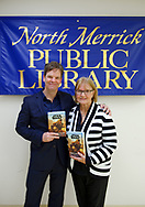 Merrick, New York, U.S.  December 20, 2019.  L-R,  Author KEVIN SHINICK has his arm around his mother LOUISE SHINICK, both holding his novel, as they pose at North Merrick Public Library banner during book signing for his STAR WARS: FORCE COLLECTOR, on Nassau County Force Collector Day. Kevin Shinick named home planet of Karr Nuq Sin, the main character of this official canon Star Wars young adult novel, MEROKIA in honor of Merokee tribe who settled his Merrick hometown on Long Island.