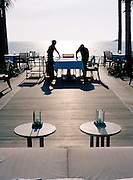 Hotel workers set tables in the late aftenroon at the 5-star Trisara Resort