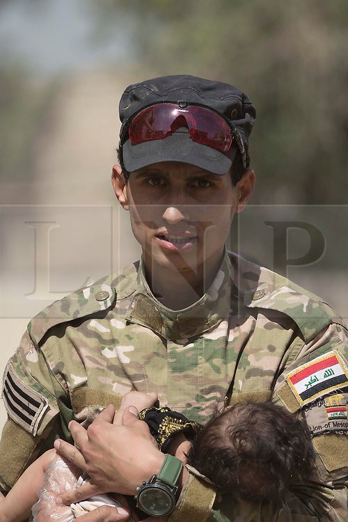 © Licensed to London News Pictures. 15/06/2017. Mosul, Iraq. An Iraqi Army soldier, of 9th Armoured Division, holds a small child as families flee from ISIS held West Mosul.<br /> <br /> Despite heavy fighting between the Islamic State and Iraqi Security Forces many civilians have started to leave ISIS territory in West Mosul. Mosul residents, many of whom have been in hiding in their homes since the start of the West Mosul Offensive, often have to run through ISIS sniper and machine gun fire to reach the safety of Iraqi Security Forces positions. Photo credit: Matt Cetti-Roberts/LNP