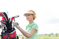 Female golfer with golf club bag against clear sky