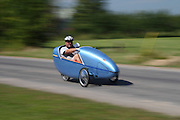 A velomobile or bicycle car is a human-powered vehicle, enclosed for protection from weather and collisions.  Here a man is peddling the velomobile in a recumbent position.  The velomobile is built on a recumbent bike frame with two steerable wheels in the front and one wheel in the back.  This tricycle design allows for a stable vehicle on wet roads.  The vehicle is air streamed to decrease wind resistance and shield the rider from rain.  As fuel consumption becomes more of an issue, more commuters will switch to human powered vehicles.