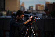 (photo by Matt Roth)<br /> Tuesday, June 5, 2012<br /> <br /> Fellow Photographer Tom McCarthy makes photos of the Transit of Venus, using sunglasses and the depth of field preview function to deaden the sun's brightness. <br /> <br /> Venus passes directly between the sun and the earth Tuesday, June 5, 2012 over the Baltimore, MD skyline. The last Transit of Venus was in 2004, but the next alignment will be in 2117.