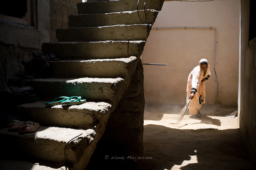A young member of Ghair Bibi's family sweeps up dirt in the alley outside their family living unit. Karachi, Pakistan, 2011