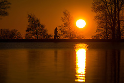 © Licensed to London News Pictures. 29/12/2016. Bradford UK. A dog walker strolls around the lake at Harold Park in Bradford at sunrise this morning on another freezing but sunny morning.Photo credit: Andrew McCaren/LNP