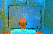 back of a person head and shoulders facing a concrete wall