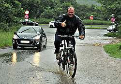 © Licensed to London News Pictures. 06/072012. Stone Staffordshire, UK. A man on his bike riding through deep water following heavy rain in Stone, Staffordshire on July 6, 2012. Heavy rain, has caused chaos and localised flooding across many part of Staffordshire today. Photo credit : Rob Leyland/LNP