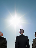 Three business people looking at the sun half length back view cropped