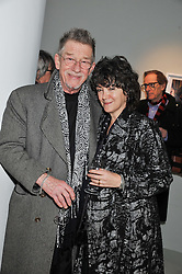 JOHN HURT and his wife ANWEN REES-MYERS at a private view of Bill Wyman - Reworked held at the Rook & Raven Gallery, 7 Rathbone Place, London W1 on 26th February 2013.