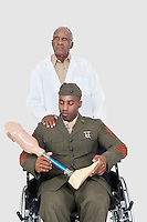 Senior doctor with US military officer holding artificial limb as he sits in wheelchair over gray background