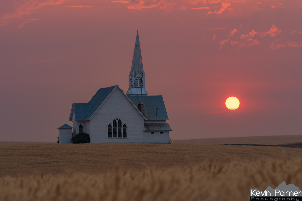 After driving for 12 hours I arrived in eastern Washington. Smoke from a nearby fire was limiting visibility over the surrounding farmland. But I knew it would lead to a very red sunset, I just had to find somewhere to shoot it. I started looking for an old barn, but instead came across this church. I liked the way it was situated between the golden wheat fields. My legs were shredded a bit as I tried to find the right spot to frame the sun. A farmer was harvesting the field as I took this, one day later and there would only be dirt instead of wheat.