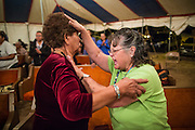 "12 JULY 2012 - FT DEFIANCE, AZ:    FLORENCE BARKER, from the Manuelito Church of God, prays for a woman during the alter call at the 23rd annual Navajo Nation Camp Meeting in Ft. Defiance, north of Window Rock, AZ, on the Navajo reservation. Preachers from across the Navajo Nation, and the western US, come to Navajo Nation Camp Meeting to preach an evangelical form of Christianity. Evangelical Christians make up a growing part of the reservation - there are now more than a hundred camp meetings and tent revivals on the reservation every year. The camp meeting in Ft. Defiance draws nearly 200 people each night of its six day run. Many of the attendees convert to evangelical Christianity from traditional Navajo beliefs, Catholicism or Mormonism. ""Camp meetings"" are a form of Protestant Christian religious services originating in Britain and once common in rural parts of the United States. People would travel a great distance to a particular site to camp out, listen to itinerant preachers, and pray. This suited the rural life, before cars and highways were common, because rural areas often lacked traditional churches.  PHOTO BY JACK KURTZ"