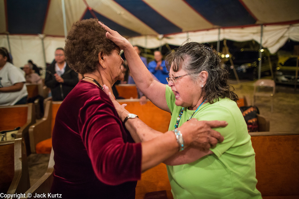 """12 JULY 2012 - FT DEFIANCE, AZ:    FLORENCE BARKER, from the Manuelito Church of God, prays for a woman during the alter call at the 23rd annual Navajo Nation Camp Meeting in Ft. Defiance, north of Window Rock, AZ, on the Navajo reservation. Preachers from across the Navajo Nation, and the western US, come to Navajo Nation Camp Meeting to preach an evangelical form of Christianity. Evangelical Christians make up a growing part of the reservation - there are now more than a hundred camp meetings and tent revivals on the reservation every year. The camp meeting in Ft. Defiance draws nearly 200 people each night of its six day run. Many of the attendees convert to evangelical Christianity from traditional Navajo beliefs, Catholicism or Mormonism. """"Camp meetings"""" are a form of Protestant Christian religious services originating in Britain and once common in rural parts of the United States. People would travel a great distance to a particular site to camp out, listen to itinerant preachers, and pray. This suited the rural life, before cars and highways were common, because rural areas often lacked traditional churches.  PHOTO BY JACK KURTZ"""