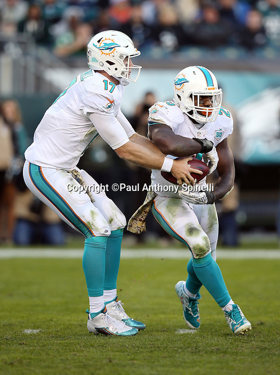 Miami Dolphins quarterback Ryan Tannehill (17) fakes a handoff to Miami Dolphins running back Lamar Miller (26) on a late fourth quarter pass play during the 2015 week 10 regular season NFL football game against the Philadelphia Eagles on Sunday, Nov. 15, 2015 in Philadelphia. The Dolphins won the game 20-19. (©Paul Anthony Spinelli)