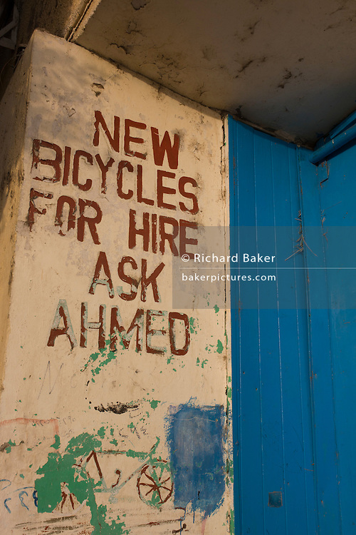 Cycle for hire sign on a wall of a travel business in the village of Bairat on the West Bank of Luxor, Nile Valley, Egypt.