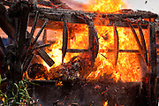 Apr. 25 -- UBUD, BALI, INDONESIA: Cokorde Gede Raka's body burns at his cremation. Cokorde, a member of Ubud's royal family, was cremated Sunday, Apr. 25. Balinese are Hindus and cremate their dead. Balinese funerals are elaborate - and expensive - affairs. A funeral for one person costs a minimum of 45 million rupiah (about $5,000 US). The body is placed into the bull's body at the cremation and cremated in the bull. The funeral pyre is burnt adjacent to the bull. That is what a family may earn in two to three years. The result is that only the rich can afford formal cremations. The body (in the casket) is placed in the top of the funeral pyre and the procession takes the body to the cremation site. The funeral pyre, and the body, are spun at intersections to confuse the spirits so the soul doesn't try to return to its home and to confuse evil spirits.    PHOTO BY JACK KURTZ