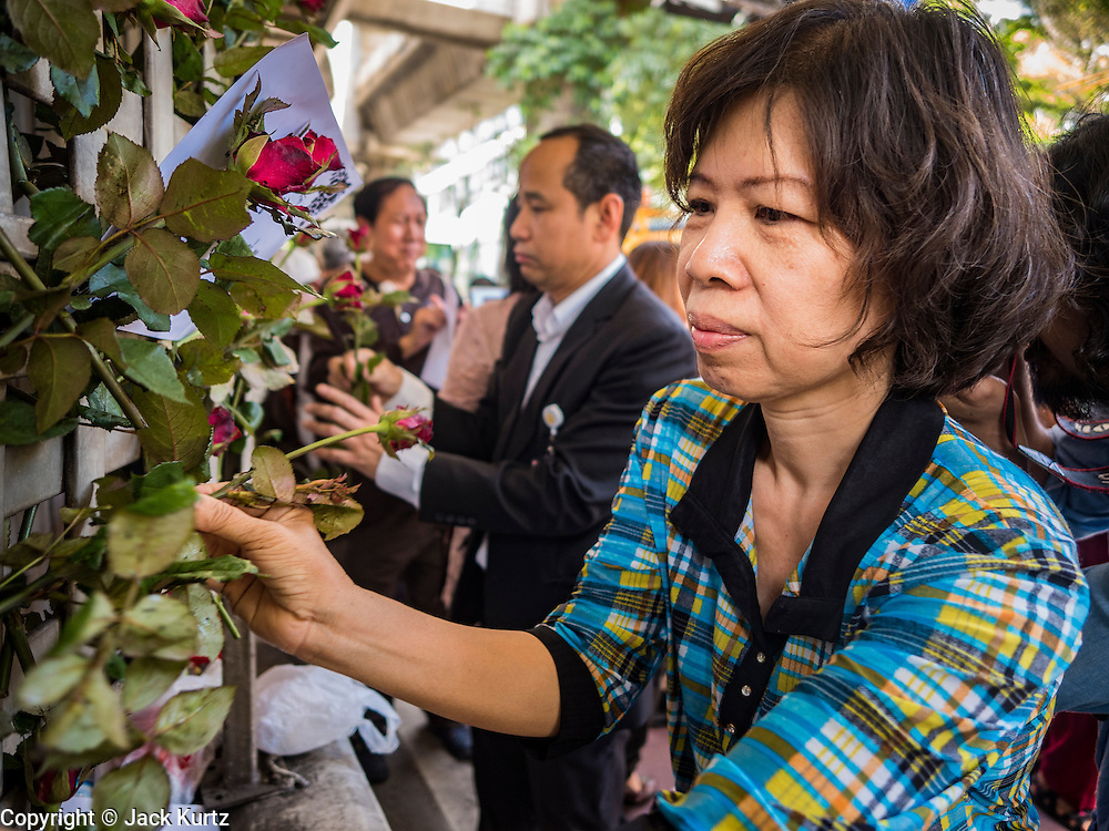 18 AUGUST 2015 - BANGKOK, THAILAND:  People leave roses at a makeshift memorial for people killed in an explosion at Erawan Shrine. The memorial is across the street from the shrine. An explosion at Erawan Shrine, a popular tourist attraction and important religious shrine in the heart of the Bangkok shopping district, killed at least 20 people and injured more than 120 others, including foreign tourists, during the Monday evening rush hour. Twelve of the dead were killed at the scene. Thai police said an Improvised Explosive Device (IED) was detonated at 18.55. Police said the bomb was made of more than six pounds of explosives stuffed in a pipe and wrapped with white cloth. Its destructive radius was estimated at 100 meters.     PHOTO BY JACK KURTZ
