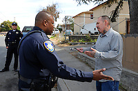 Salinas police officers Jeffrey Lofton listens to a Fremont Street resident as Richard Lopez looks on. The Community Alliance for Safety and Peace is an ambitious program that aims to steer youth away from gang violence and toward solutions offered by more than 30 local organizations offering alternatives.
