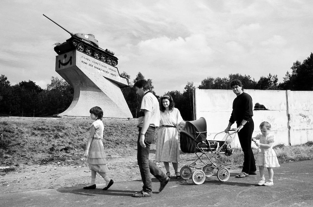 Deutschland - GERMANY - Mauerfall - 1990 -  Die Berliner Mauer verschwindet aus dem Stadtbild, die Mauer wird abgerissen/abgetragen : HIER:   DDR-Grenzübergang Dreilinden im Süden Berlins; Ehrenmal mit Panzer für die Sowjetische Armee; Graffiti - Familienausflug auf dem ehemaligen Todesstreifen; 09/1990.1990 - FALL OF THE BERLIN WALL - the wall disappears, is demolished; HERE: GDR Border in Dreilinden - Memorial wit a tank for the Red Army, the Soviet Military; Graffiti - Family Excursion at the former death strip... 08/1990.copyright: Christian Jungeblodt