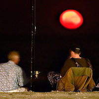 (PFEATURES) Avone By The Sea 6/3/2004  L-R David Carson Mitchell and Mark Decaro both of Avon By The Sea sit and fish near the waters edge as a wicked orange moon rises in the east.   Michael J. Treola Staff Photographer......MJT