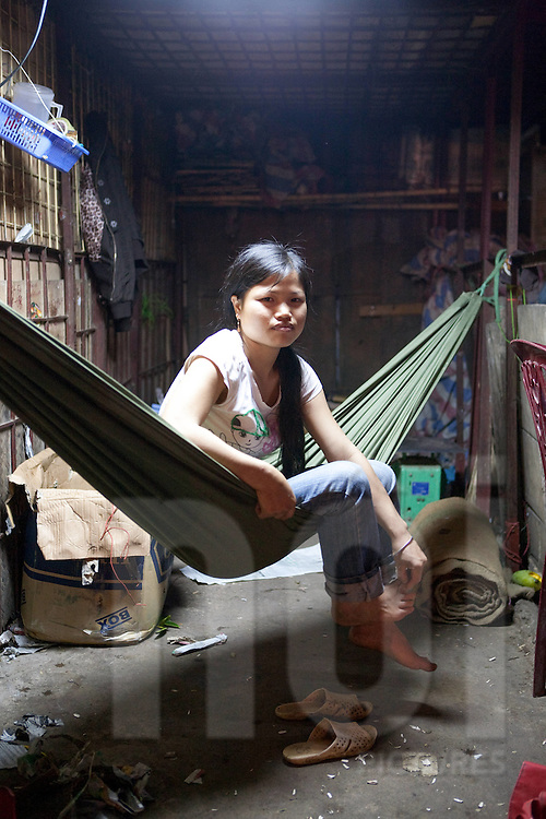A seller at the Long Bien night market gets up from a nap. Hanoi, Vietnam, Southeast Asia