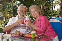 Elderly couple with drinks in garden