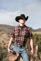 All American Cowboy holding a saddle outdoors