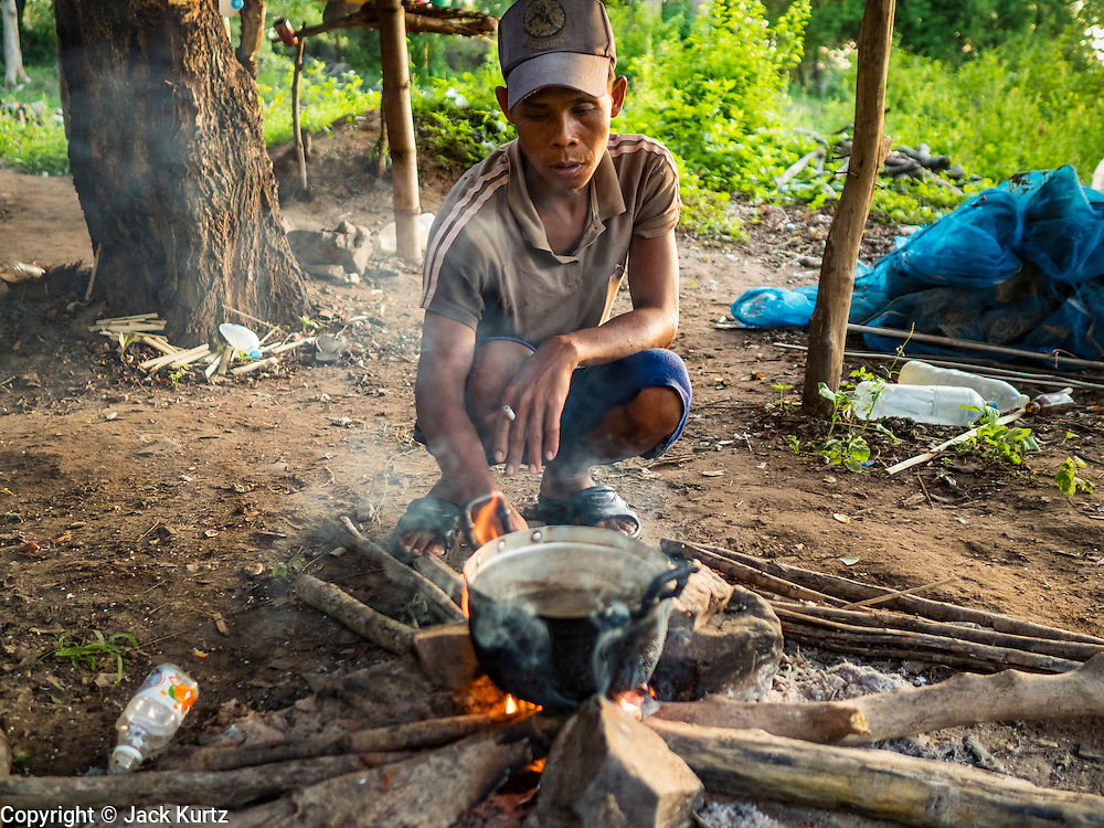 19 JUNE 2016 - DON KHONE, CHAMPASAK, LAOS: A fisherman boils water to make instant coffee in the fishermen's shelter at Khon Pa Soi Waterfalls, on the east side of Don Khon. It's the smaller of the two waterfalls in Don Khon. Fishermen have constructed an elaborate system of rope bridges over the falls they use to get to the fish traps they set. Fishermen in the area are contending with lower yields and smaller fish, threatening their way of life. The Mekong River is one of the most biodiverse and productive rivers on Earth. It is a global hotspot for freshwater fishes: over 1,000 species have been recorded there, second only to the Amazon. The Mekong River is also the most productive inland fishery in the world. The total harvest of fish from the Mekong is approximately 2.5 million metric tons per year. By some estimates the harvest in the Tonle Sap (in Cambodia) had doubled from 1940 to 1995, but the number of people fishing the in the lake has quadrupled, so the harvest per person is cut in half. There is evidence of over fishing in the Mekong - populations of large fish have shrunk and fishermen are bringing in smaller and smaller fish.     PHOTO BY JACK KURTZ
