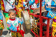 "05 JULY 2014 - BANGKOK, THAILAND:  A boy plays a cymbal in Bangkok during a parade for vassa. Vassa, called ""phansa"" in Thai, marks the beginning of the three months long Buddhist rains retreat when monks and novices stay in the temple for periods of intense meditation. Vassa officially starts July 11 but temples across Bangkok are holding events to mark the holiday all week.   PHOTO BY JACK KURTZ"