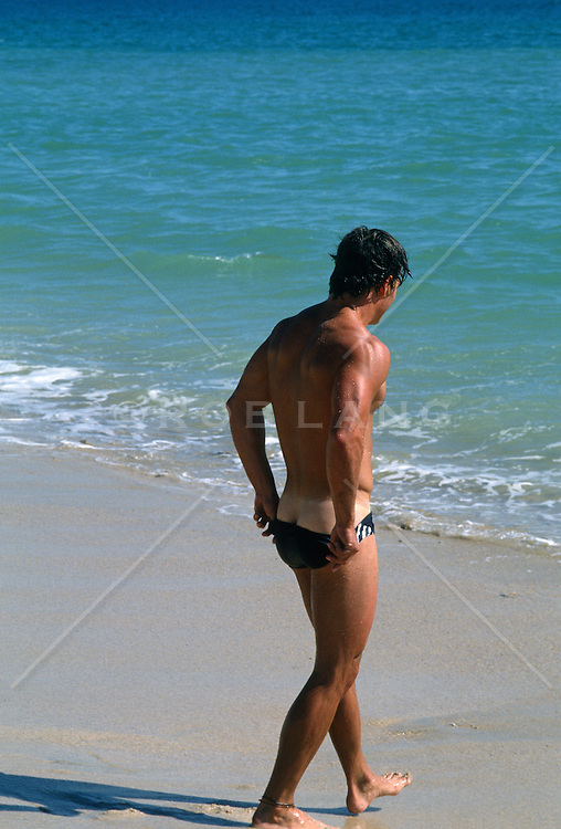 Man walking into the ocean while pulling up his speedo