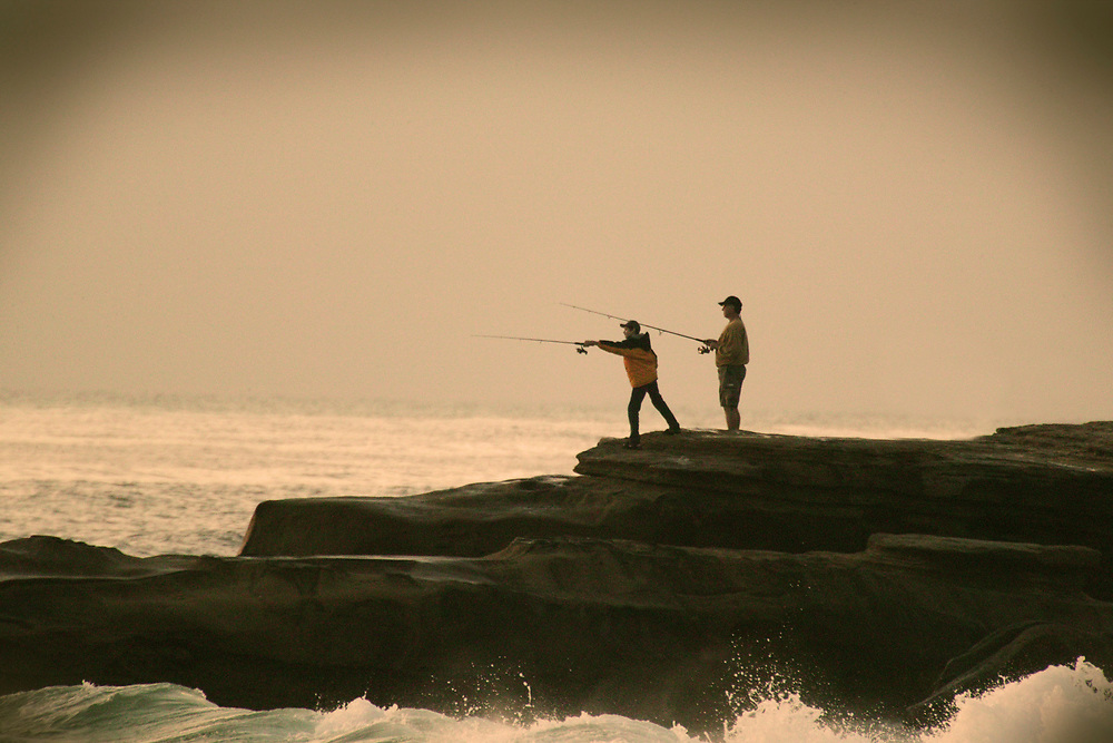 Father and son surfcasting from rocks
