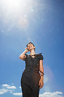 Woman using mobile phone standing against sky low angle view