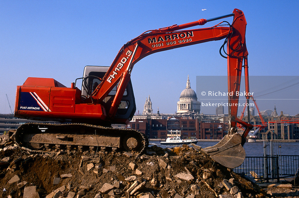 The hydraulic arm of a Fiat-Hitachi caterpillar digger frames the 17th Century dome of St Paul's Cathedral during the redevelopment of the southbank in central London. Standing on a pile of rubble it sits idol during a break in reconstruction project that transformed Bankside from an unlandscaped are to a smart walkway in time for the Millennium of 2000. An aircraft en-route to City Airport flies overhead and a Police river patrol boat cruises past too.