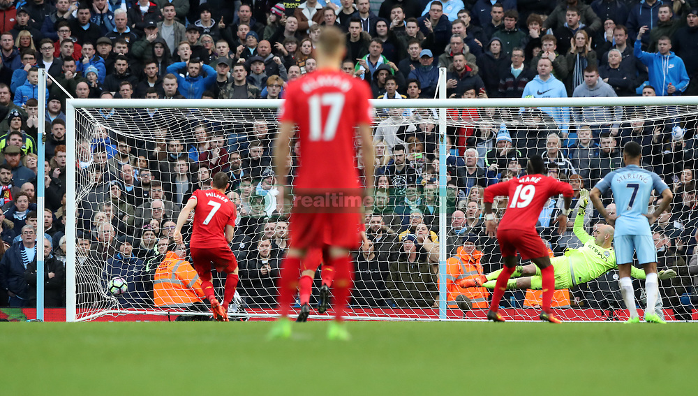 Liverpool's James Milner (left) scores his side's first goal of the game during the Premier League match at the Etihad Stadium, Manchester.