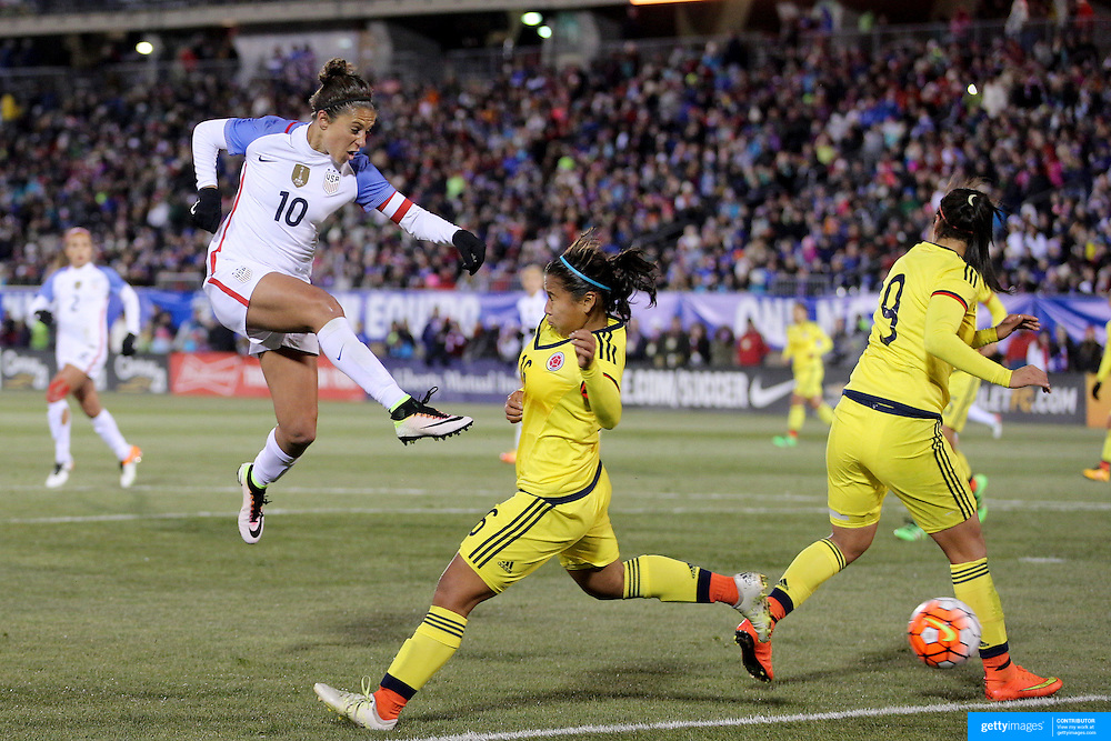 Carli Lloyd, (left), USA, shoots past Leicy Santos and Orianica Velasquez, (right), Colombia during the USA Vs Colombia, Women's International friendly football match at the Pratt & Whitney Stadium, East Hartford, Connecticut, USA. 6th April 2016. Photo Tim Clayton