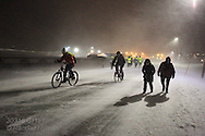 People brave snowstorm to bike and walk along main road during the months-long polar night in Longyearbyen, Svalbard, Norway.