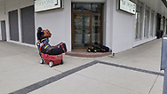 A man pulls a wagon containing his possessions past a man sleeping in front of a door during the covid-19 pandemic in March 2020 in  Windsor, Ontario.