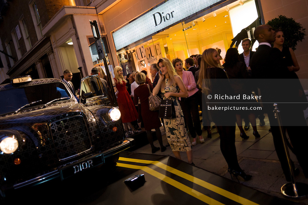 A young woman makes a call in the street near the outdoor set with a sponsored taxi cab for the Christian Dior fashion house in London's Bond Street during Vogue's Fashion's Night Out festival in the streets of the West End. The specially designed raised ramp has on it a Dior-sponsored taxi cab placed upon it, complete with fake double-yellow lines. It is early evening and crowds are gathering for this PR event to promote retail couture, bringing in thousands for this fashion fest.