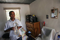 Wilfrido Galarraga, 21, plays his trumpet in his bedroom in his home in La Vega, a poor shanty town on the outskirts of Caracas, Venezuela.  Galaragga is part of the Venezuela Simon Bolivar Youth Orchestra, which is part of a music program encompassing more than 200,000 Venezuelan youth.  The program is meant to help underprivileged youth.