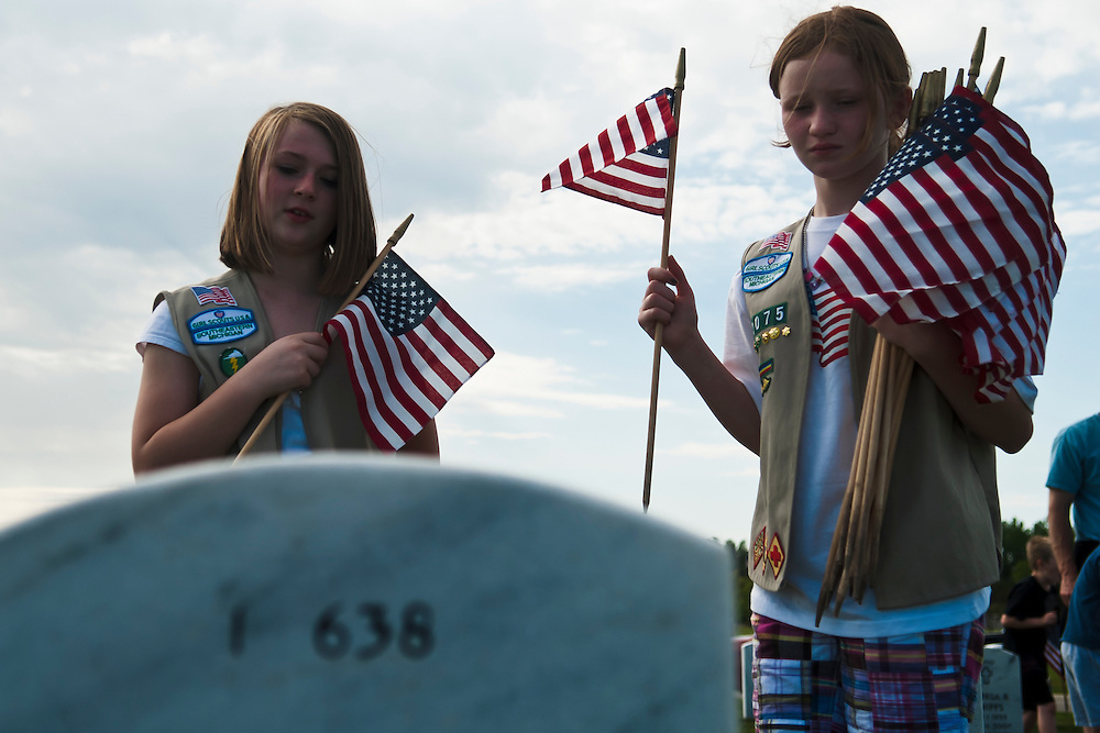 Lathan Goumas | MLive.com..Hannah Morawski, 12, and Maris Humphreys, 12, both of Davisburg, read a headstone before placing a flag in front for the Memorial Day weekend at the Great Lakes National Cemetery in Holly, Mich. on Friday May 25, 2012.