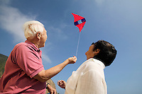 Couple flying kite outdoors (low angle view)