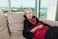 Portrait of girl in vampire costume relaxing on sofa at home