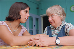 Teenage girl with physical disability sitting at kitchen table in residential respite care home holding hands and talking with carer,