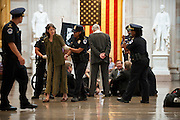 A group of religious leaders protest in the Rotunda of the U.S. Capitol against the proposal by House Speaker John Boehner to cut some $917 billion in federal spending in exchange for a debt ceiling hike.