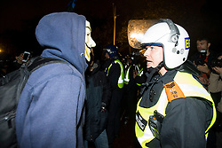 © Licensed to London News Pictures. 05/11/2015. London, UK. A demonstrator comes face to face with a police officer in riot gear during An anti-capitalist  protest organised by the group Anonymous outside Parliament in Westminster on bonfire night 05, November 2015. Bonfire night, also known as Guy Fawkes night, is an annual commemoration of when Guy Fawkes, a member of the Gunpowder Plot, was arrested for attempting to blow up the House of Lords at parliament.   Photo credit: Ben Cawthra/LNP