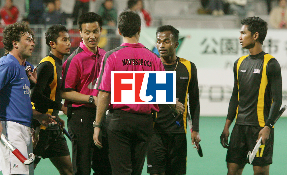 Kakamigahara, Gifu-Japan : Italian and Malaysian players seen in discussion with umpire Chen Dekang of China and Montes de Oca of Argentina, over the last minute equaliser by Malaysia in the Olympic Hockey Qualifier at Gifu Perfectural Green Stadium at Kakamigahara on 06 April 2008. <br /> Malaysia drew with Italy 4-4. <br /> Photo: GNN/ Vino John