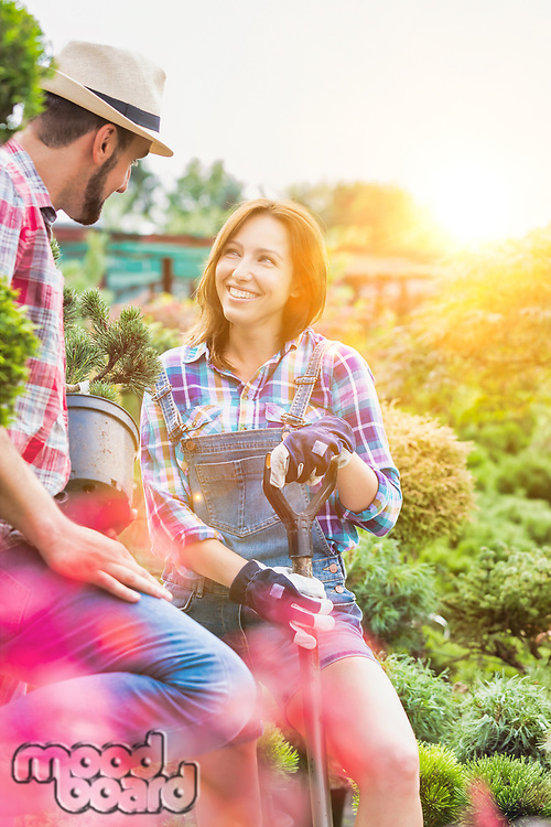 Portrait of beautiful gardener smiling while talking to coworker in shop