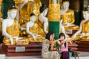 15 JUNE 2013 - YANGON, MYANMAR: Tourists take pictures of themselves in front of a hall of Buddha statues at Shwedagon Pagoda. The Shwedagon Pagoda is officially known as Shwedagon Zedi Daw and is also called the Great Dagon Pagoda or the Golden Pagoda. It is a 99 metres (325 ft) tall pagoda and stupa located in Yangon, Burma. The pagoda lies to the west of on Singuttara Hill, and dominates the skyline of the city. It is the most sacred Buddhist pagoda in Myanmar and contains relics of the past four Buddhas enshrined: the staff of Kakusandha, the water filter of Koṇāgamana, a piece of the robe of Kassapa and eight strands of hair fromGautama, the historical Buddha. The pagoda was built between the 6th and 10th centuries by the Mon people, who used to dominate the area around what is now Yangon (Rangoon). The pagoda has been renovated numerous times through the centuries. Millions of Burmese and tens of thousands of tourists visit the pagoda every year, which is the most visited site in Yangon.  PHOTO BY JACK KURTZ