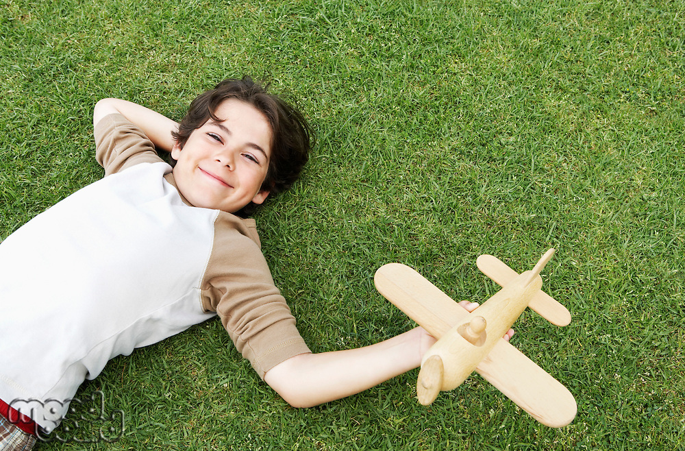 Smiling Pre-teen boy lying on back in grass arm behind head holding toy airplane elevated view