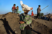 A boy is holding a hen while others are playing around the abandoned evaporation pool that was once used by Union Carbide (now DOW Chemical) next to their industrial complex, site of the infamous 1984 gas tragedy in Bhopal, Madhya Pradesh, central India. The poisonous cloud that enveloped Bhopal left everlasting consequences that today continue to consume people's lives. Thousands tons of hazardous chemical waste are still buried in various spots around this area of Bhopal.