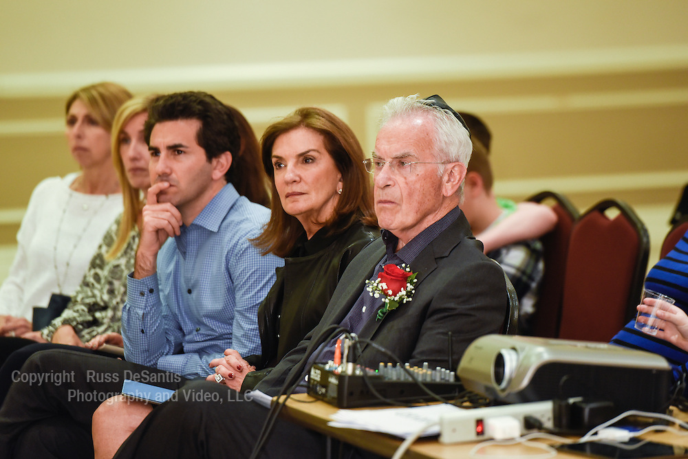 Holocaust survivor Michael Kaplan, (right), Highland Park, spoke during the ceremony. Here, he sits with his family and listens to another survivor speak. The Center of Jewish Life in Marlboro, NJ, held a ceremony to mark Holocaust Remembrance Day on Thursday, April 16,2015. /Russ DeSantis/Special to the Asbury Park Press / SLUG-asb 0417 holocaust remembrance